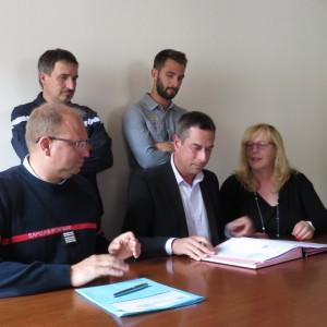 Le colonel Hugues Deregnaucourt, Stssy Speissmann et Elizabeth Klipfel (au premier plan) signent la convention sous les yeux des deux principaux intéressés
