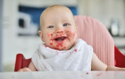 baby in the kitchen with food around his mouth